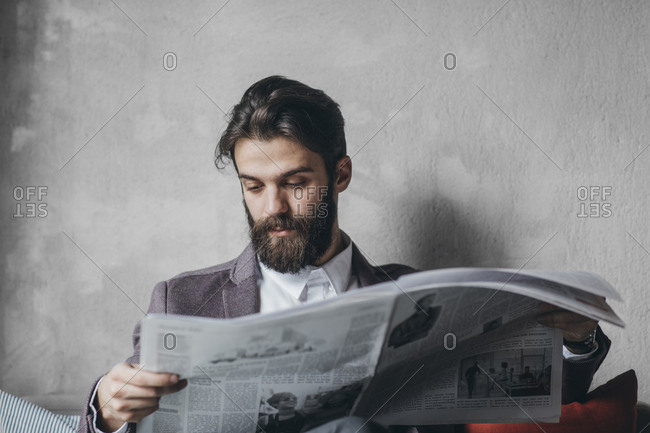 Handsome businessman with beard reading newspapers at cafe
