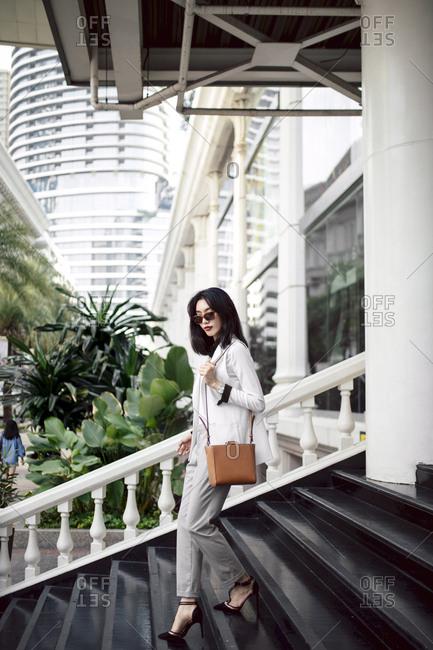 Elegant Asian businesswoman walking down the stairs