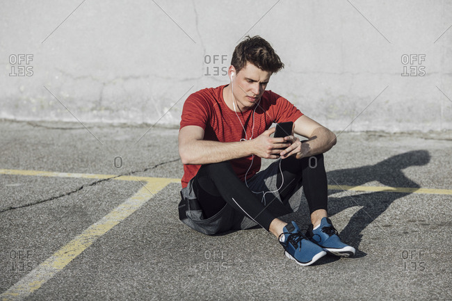 Portrait of handsome sportsman listening to music on earphones and holding cell phone