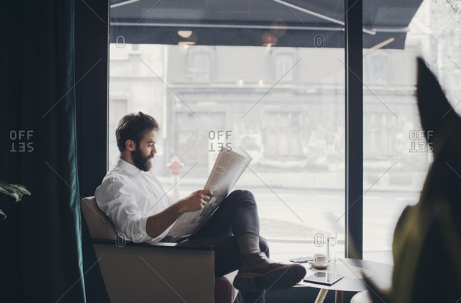Businessman reading newspapers at coffee shop