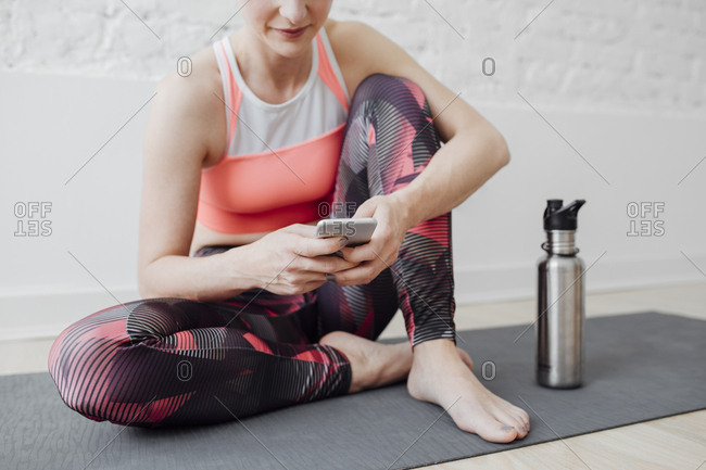 Cropped sportswoman sitting on mat and typing on cell phone
