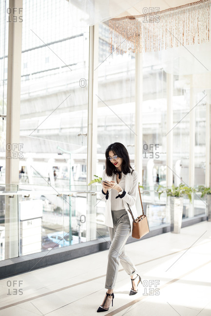 Elegant smart Asian businesswoman walking at shopping mall and typing on cell phone