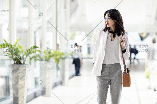 Elegant Asian businesswoman standing at shopping mall