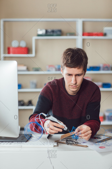 Graphic designer using 3d printing pen at office