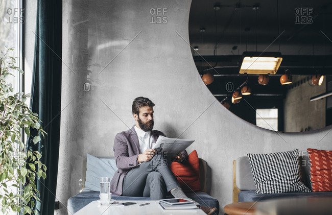 Handsome businessman reading newspapers at cafe
