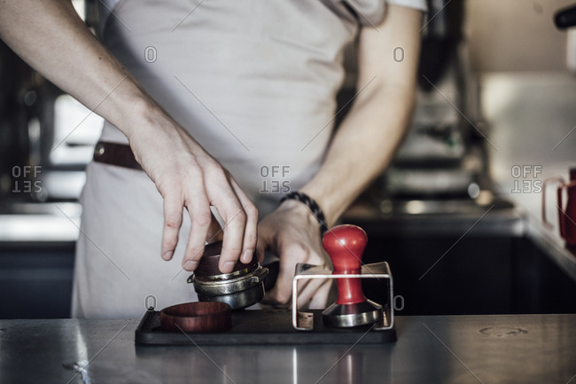 Hands of unrecognisable barman using espresso filter