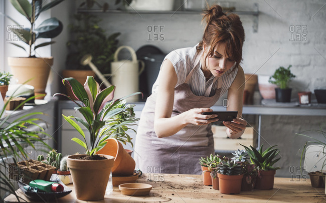 Female florist taking photo of plants in pots with cell phone