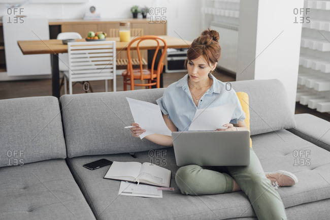 Woman holding laptop in her lap and reading from papers and sitting at home