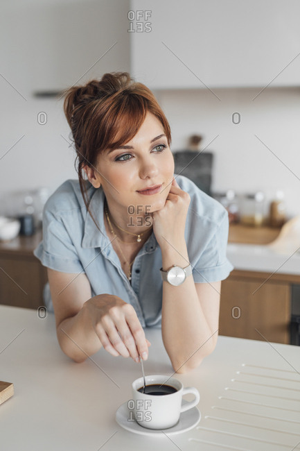 Beautiful redheaded woman standing at kitchen and enjoying  morning coffee