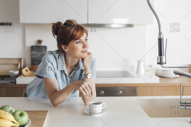 Pretty redheaded woman standing at kitchen and enjoying  morning coffee