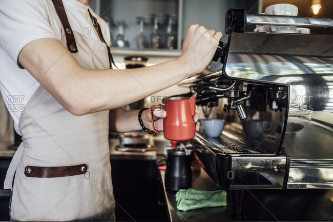 Hands of unrecognisable barmen making coffee with milk