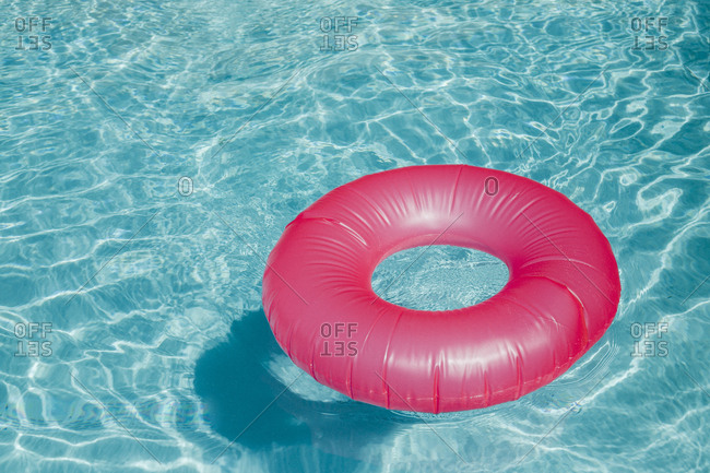 Pink inner tube floating in a blue pool