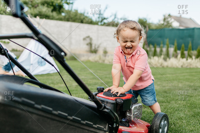 Portrait of a young child with his eyes closed and tongue out standing at a lawn mower. Toddler boy having fun cutting grass.