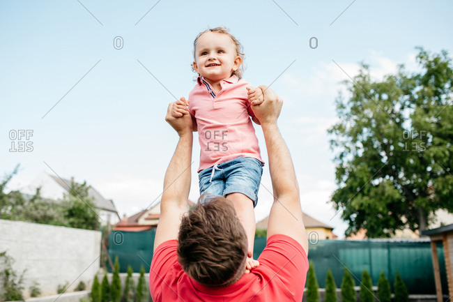 Father playing with his son outside in the garden. Happy child having fun with his father.