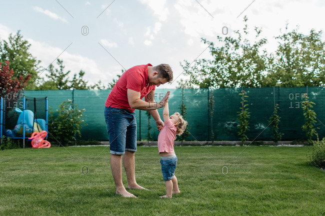 Father and a son giving a high five to each other outside in a garden. Cheerful father having fun with his toddler boy.