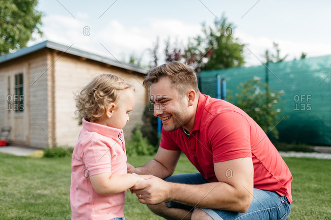 Happy father looking with love at his son outside in the garden. Child having fun with his father on a sunny summer day.