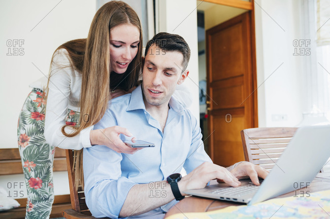 Young couple using laptop computer and smartphone at home