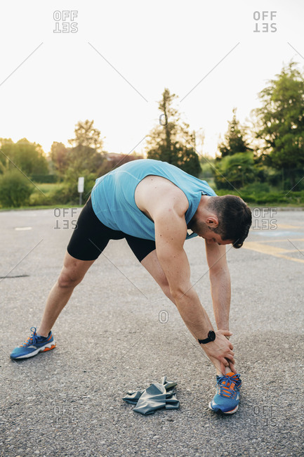 Young man outdoor stretching outside wearing sport watch