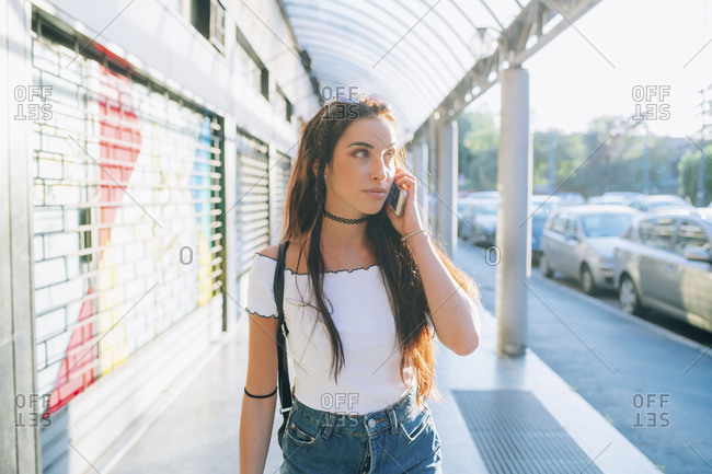Young woman outdoor walking talking smart phone