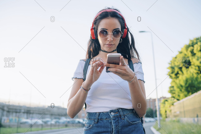 Young woman outdoors walking and listening to music using smart phone