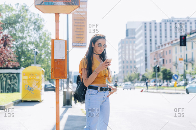 Young woman outdoors waiting at bus stop using smart phone