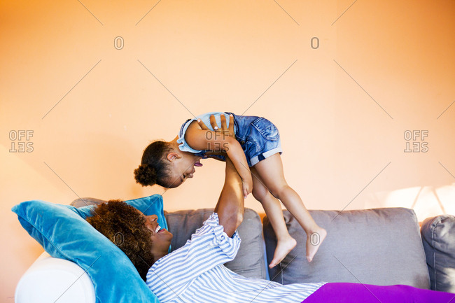 Side view of happy mother lifting daughter while lying on sofa at home