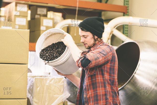 Worker Filling Box With Coffee Beans In Factory