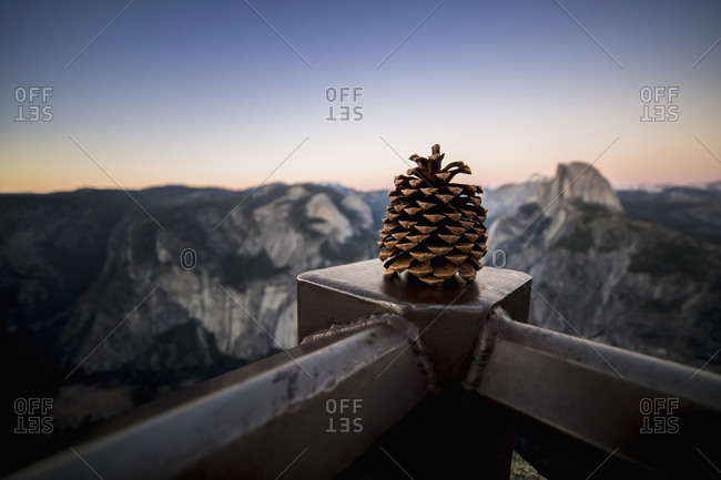 Pine Cone On Metal Railing Against Mountains