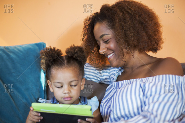 Smiling mid adult woman looking at daughter using digital tablet at home