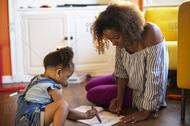 Mid adult woman with daughter drawing with crayons in book