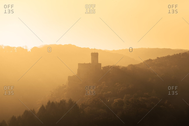 Hilly landscape with the castle Pyrmont in the centre of the picture, flooded by the rays of the setting sun.