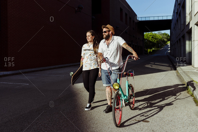 Trendy couple with tattoos walking on the street with a skateboard and a vintage bicycle