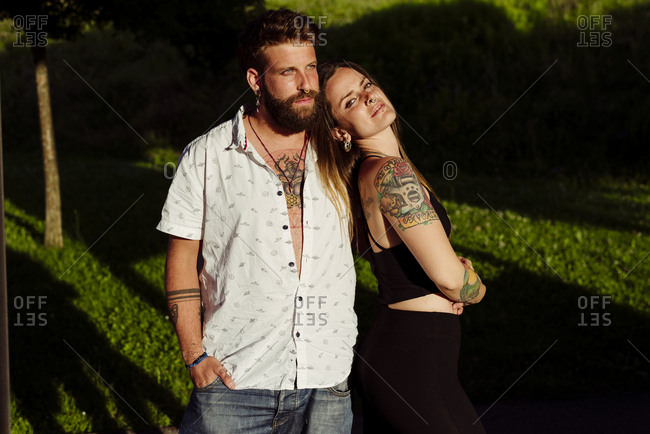 Tattooed young attractive couple standing in the park looking at the camera