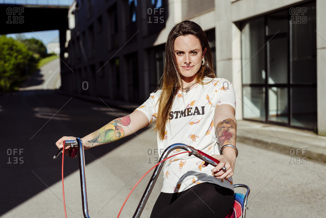 Trendy tattooed woman sitting on a vintage bicycle in the middle of the street