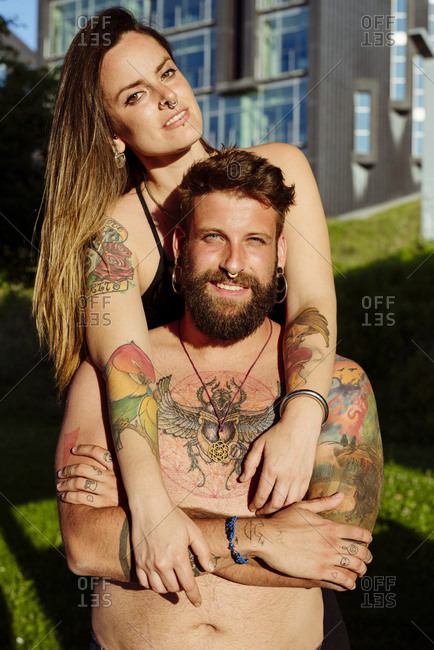 Shirtless and tattooed young attractive couple standing in the park looking at the camera