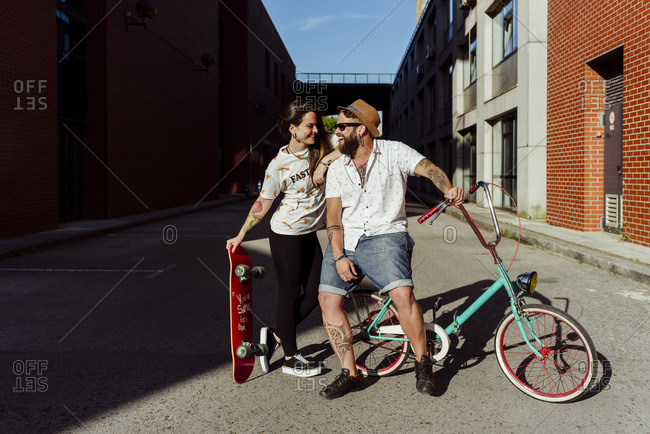 Trendy couple with tattoos standing on the street with skateboard and vintage bicycle looking at the camera