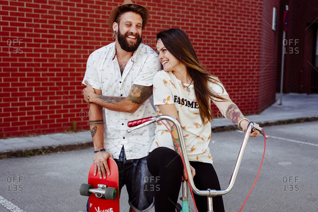 Trendy couple with tattoos standing on the street with skateboard and vintage bicycle