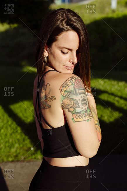 Portrait of an attractive young woman with tattoos in the park looking down