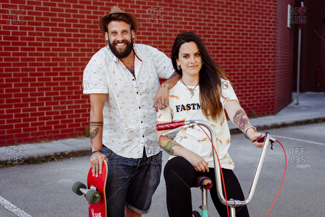 Trendy couple with tattoos standing on the street with skateboard and vintage bicycle looking at camera