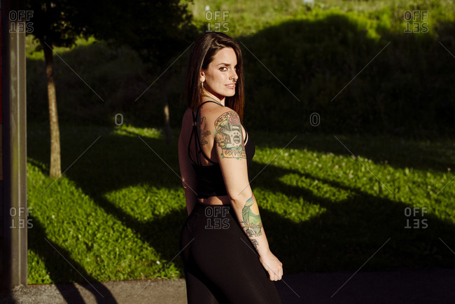 Portrait of an attractive young woman with tattoos in the park looking away