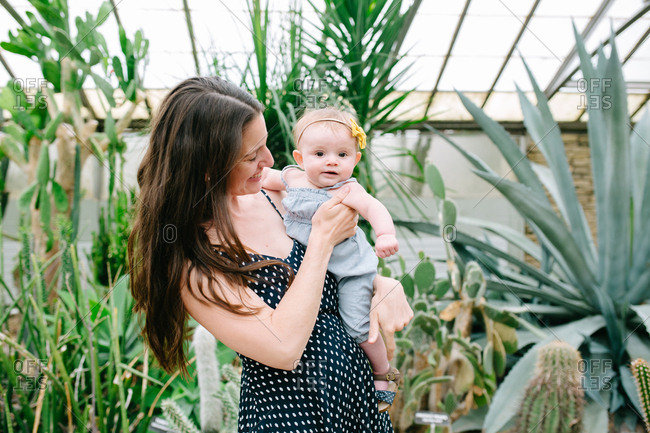 Mother holding baby in a botanical garden