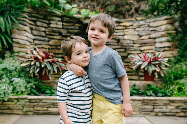 Two boys hugging at a botanical garden