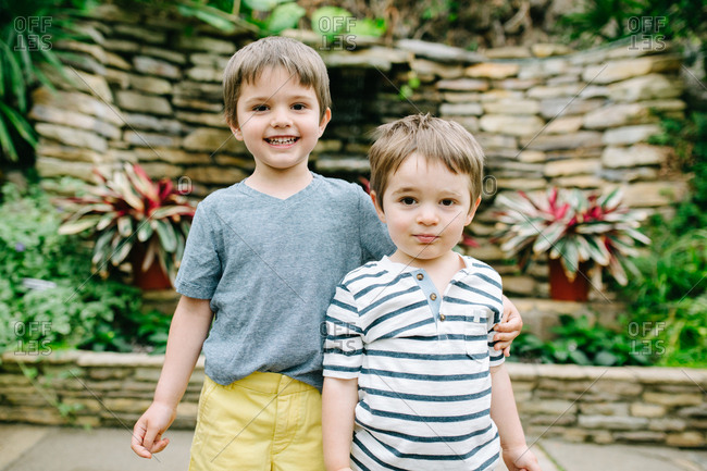 Two brothers hugging at a botanical garden