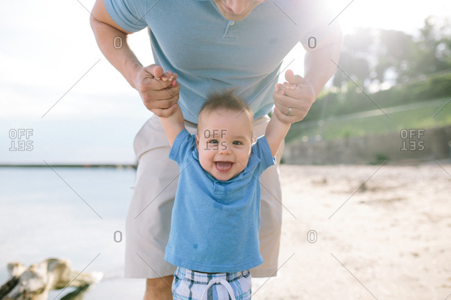 Happy baby holding parents hands on a beach