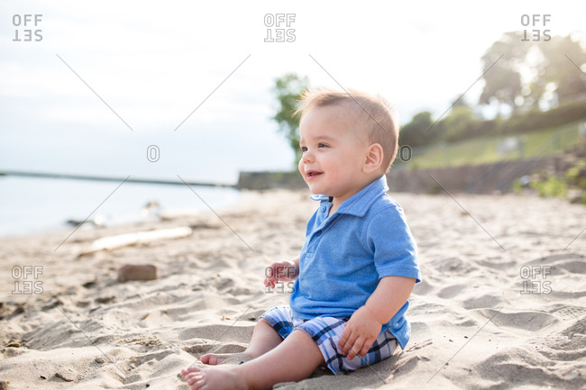 Happy mother holding baby boy on a beach