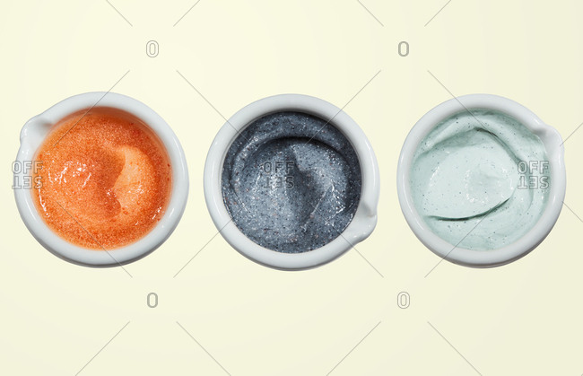 Three containers with different types of skincare scrubs