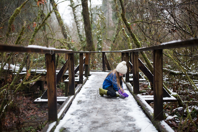 Girl making snowball on snow covered walkway