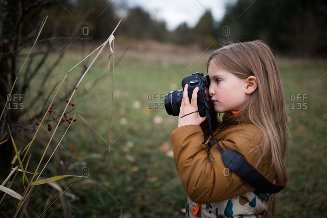 Girl taking a picture of a plant