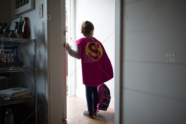 Girl wearing cape standing in doorway and holding backpack