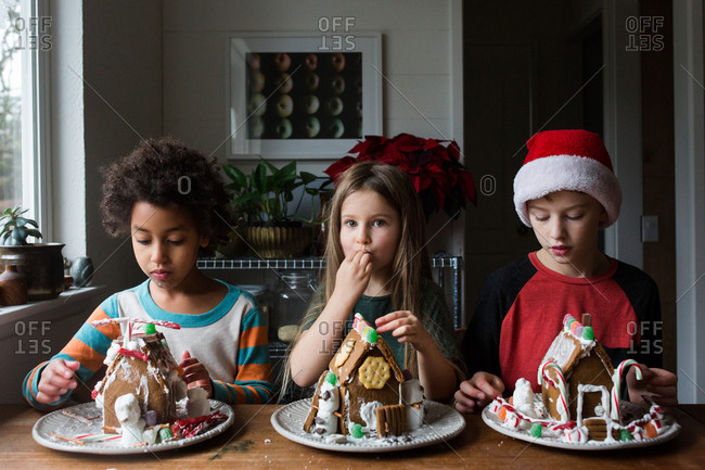 Siblings with decorated gingerbread houses sitting together